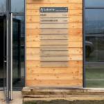 Signalétique d'entrée de bâtiment réalisé en plexi imprimé en vitrophanie et fixé par entretoise